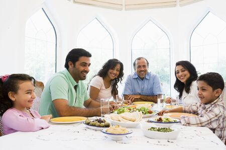 Family sitting at dinner table smiling (high key) Stock Photo - 3186953
