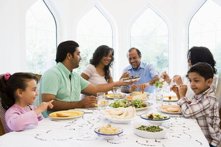 Family sitting at dinner table smiling (high key) Stock Photo - 3186928