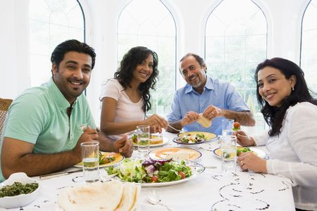 Two couples sitting at dinner table smiling (high key) Stock Photo - 3274246