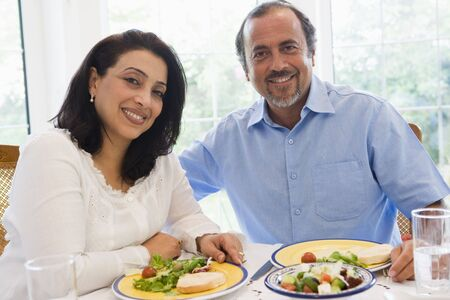 Couple sitting at dinner table smiling (high key) photo