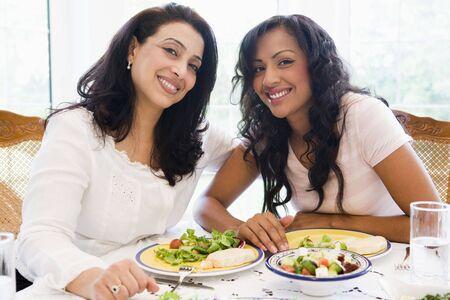 high key: Due donne sedute a tavola sorridente (alta chiave)  Archivio Fotografico