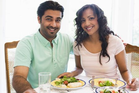dinners: Couple sitting at dinner table smiling (high key)