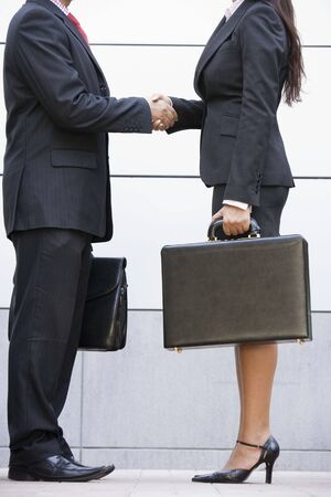 company profile: Two businesspeople standing outdoors holding briefcases and shaking hands