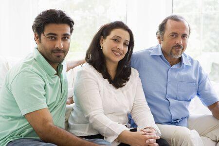 Two men and a woman sitting in living room smiling (high key) Stock Photo - 3186692