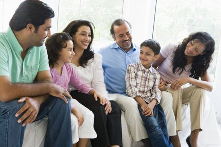 Family sitting in living room smiling (high key) Stock Photo - 3246637