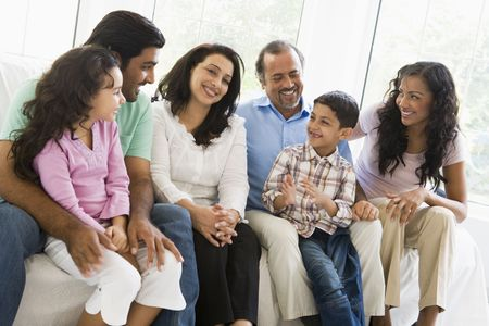 Family sitting in living room smiling (high key) Stock Photo - 3273916
