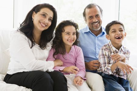 Grandparents sitting in living room with grandchildren smiling (high key) Stock Photo - 3186581