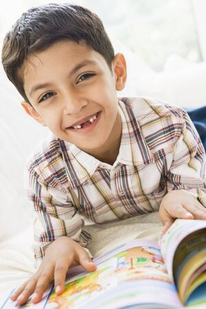 elementary age boy: Young boy in living room reading a book and smiling (high key)