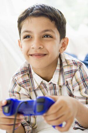 playing video games: Chico joven en la sala de juegos de video y sonriente (clave de alta  selectiva enfoque)  Foto de archivo