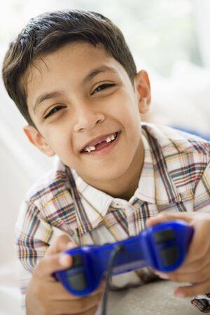 jugando videojuegos: Chico joven en la sala de juegos de video y sonriente (clave de alta  selectiva enfoque)  Foto de archivo
