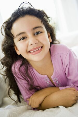 Young girl in living room smiling (high key)