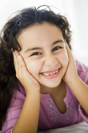 parlours: Young girl in living room smiling (high keyselective focus)