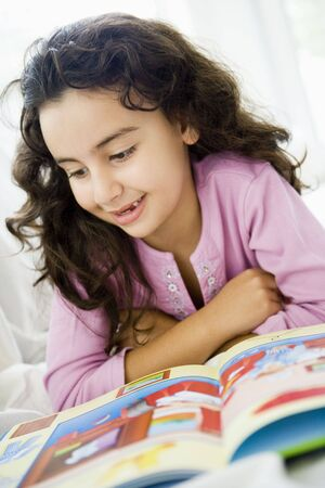 parlours: Young girl in living room reading book and smiling (high keyselective focus)