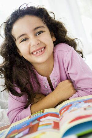 Young girl in living room with book smiling (high key/selective focus)