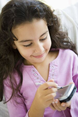 parlours: Young girl in living room with personal digital assistant smiling (high keyselective focus)