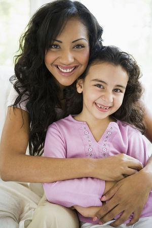 Mother and daughter in living room smiling (high key)