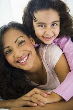 peacefulness: Mother and daughter in living room embracing and smiling (high keyselective focus)