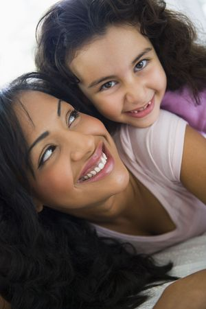 Mother and daughter in living room embracing and smiling (high keyselective focus) photo
