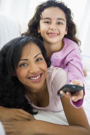 Mother and daughter in living room with remote control smiling (high key/selective focus)