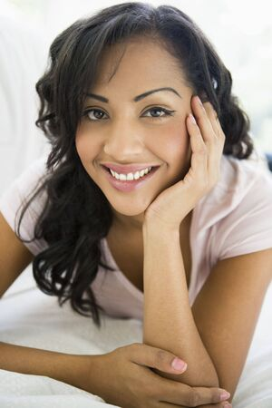 Woman in living room smiling (high keyselective focus) photo