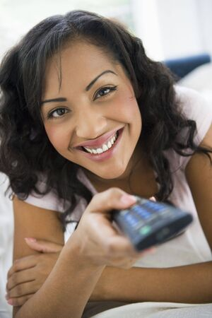 Woman in living room holding remote control smiling (high key/selective focus) photo