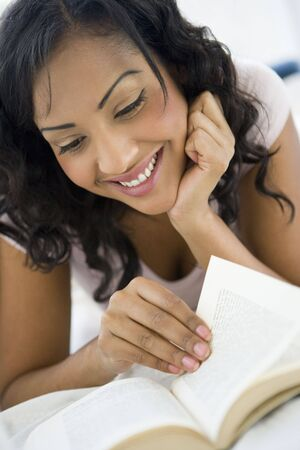 Woman in living room with book smiling (high keyselective focus) photo