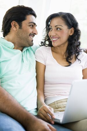 Couple in living room with laptop smiling (high keyselective focus)