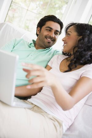 Couple in living room with laptop smiling (high keyselective focus) photo