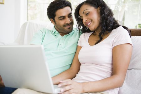 caucasoid race: Couple in living room with laptop smiling (high keyselective focus)
