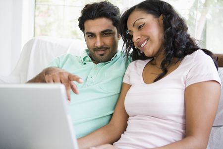Couple in living room with laptop pointing and smiling (high keyselective focus) Stock Photo