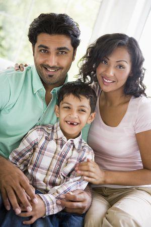 high key: Famiglia in salotto seduta sul divano sorridente (alta chiave)  Archivio Fotografico