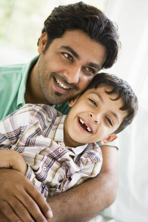 Father and son in living room smiling (high key) Stock Photo
