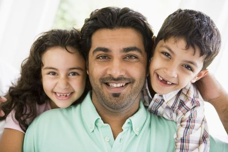 Father and two young children in living room smiling (high key) photo