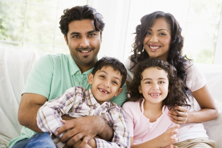 Family in living room sitting on sofa smiling (high key) Stock Photo - 3246634