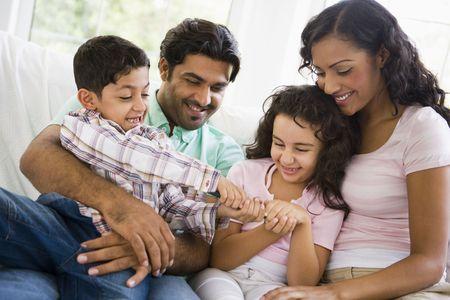 familia unida: Familia en sala de la lucha por control remoto sonriente (clave de alta)