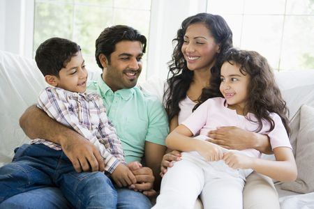 Family in living room sitting on sofa smiling (high key) Stock Photo - 3246630