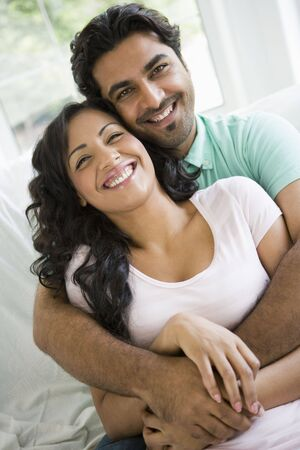 offset angles: Couple in living room embracing and smiling (high key)
