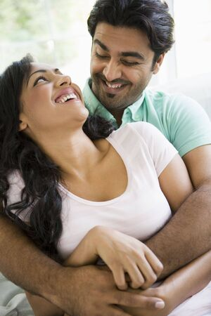caucasoid race: Couple in living room embracing and smiling (high key)