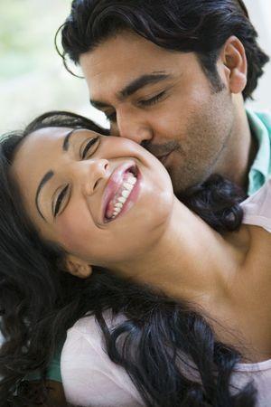 pareja abrazada: Pareja en sala de abrazar y sonre�r (clave de alta)