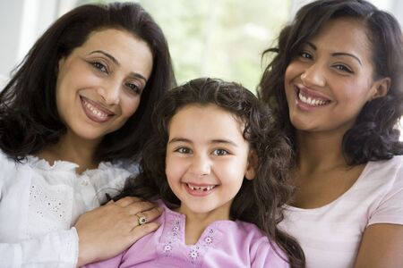 3 generation: Two women and young girl in living room embracing and smiling (high key) Stock Photo