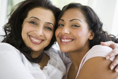 parlours: Two women in living room embracing and smiling (high key) Stock Photo