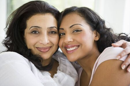Two women in living room embracing and smiling (high key) photo