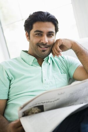 Man in living room with newspaper smiling (high key/selective focus) photo