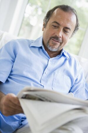 periodicals: Man in living room with newspaper (high keyselective focus)