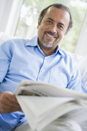 Man in living room with newspaper smiling (high keyselective focus) photo