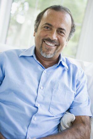 closeups: Man sitting in living room smiling (high keyselective focus)