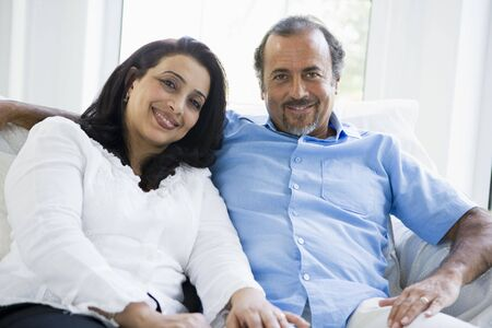 Couple sitting in living room smiling (high key) photo