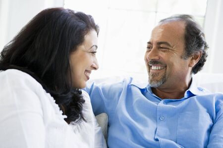 Couple sitting in living room smiling (high key) Stock Photo - 3186666