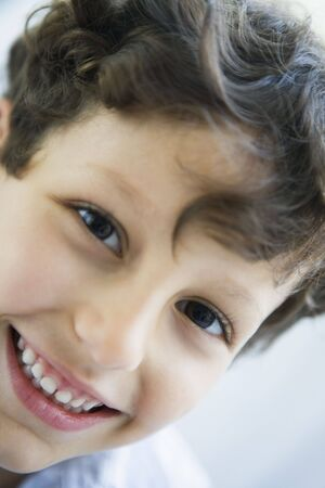 Young boy indoors smiling (high key)