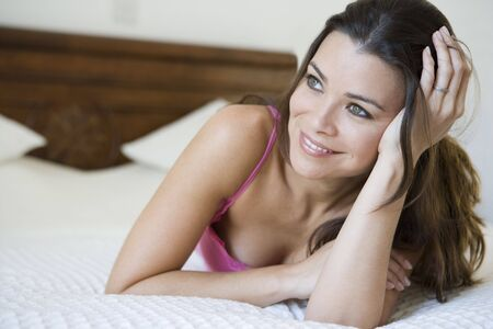 Woman relaxing on bed in bedroom smiling (selective focus) Stock Photo - 3186733